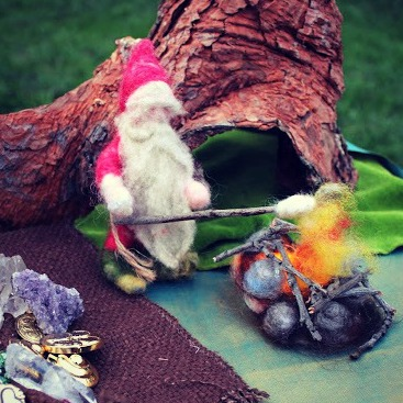 130925 Needle-felted Grumpy Red Gnome roasting marsh mellows over open kindling fire pit. Square cropped.