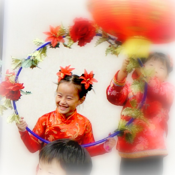 C Hexinnian Greeter in a flower garland arch hoop. First Graders' Chinese New Year of the Dragon 2012 stage dance performance at the Barclay Theater. Learn Mandarin Chinese with free, fun and beautiful resources