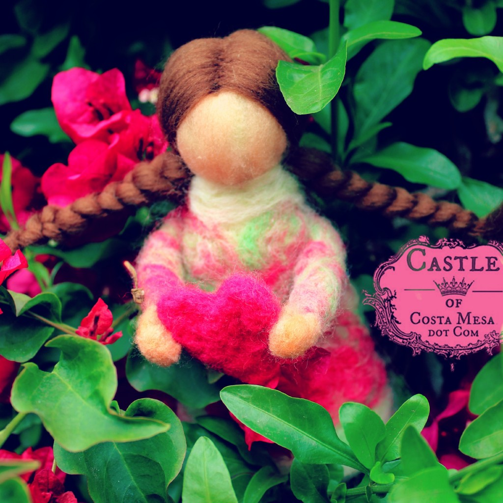 140121 Lisa'a needle-felted guardian doll with heart and 2 brown braids peeking from honeysuckle bushes. Square cropped.