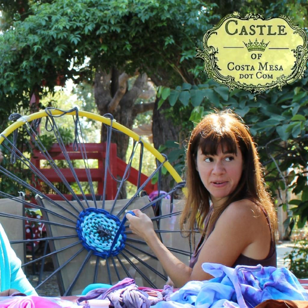 140922 Isa weaving T-shirt yarn bath rug on hula hoop loom with sun shining on top of her hair 2