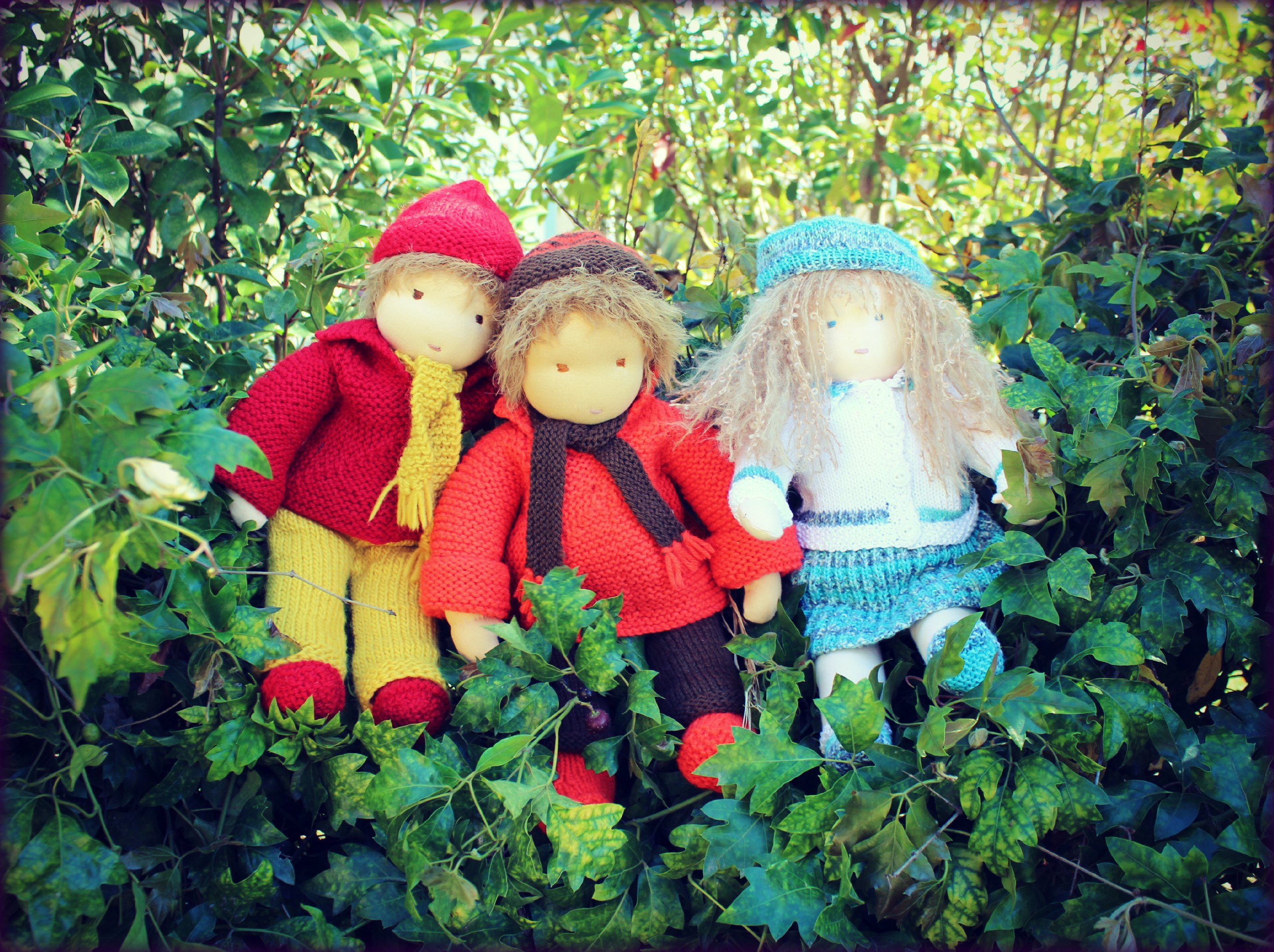 121219 Christine Newell's 3 16 inch Waldorf dolls sitting on a berry fence