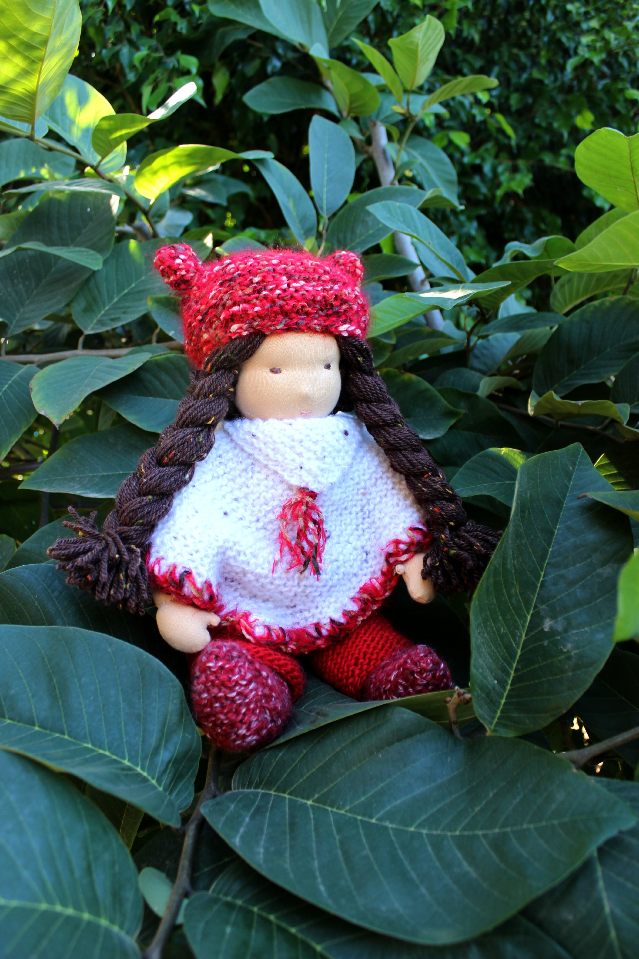 121219 Yvonne's 16 inch Waldorf cuddle doll dark brown hair with long braids and white poncho on cherimoya tree