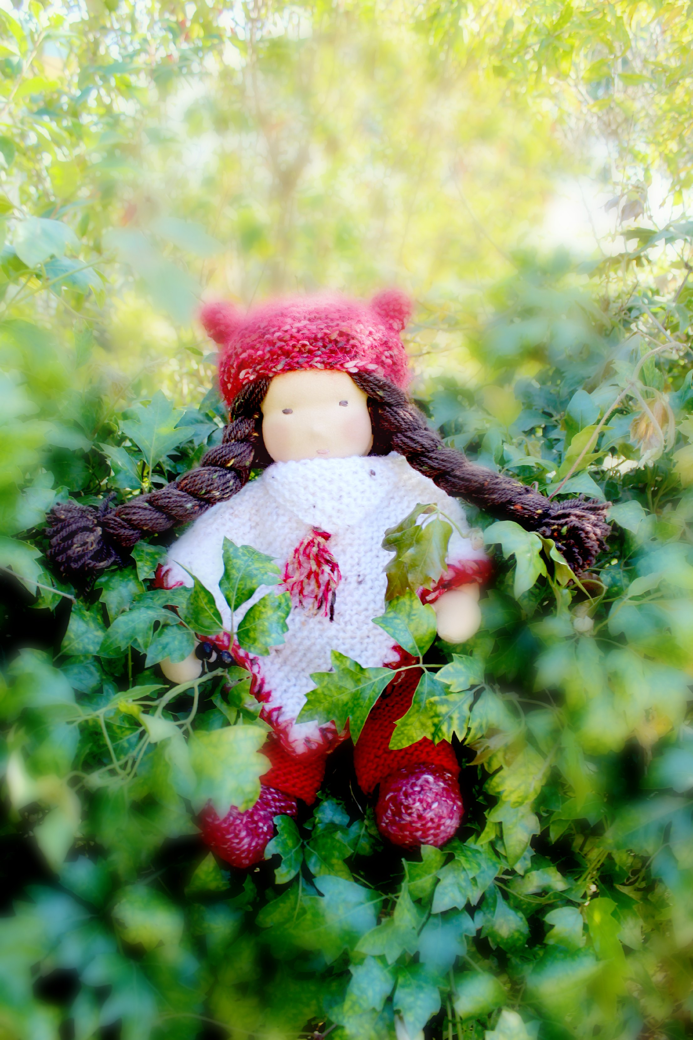 121219 Yvonne's 16 inch Waldorf cuddle doll sitting on a berry fence