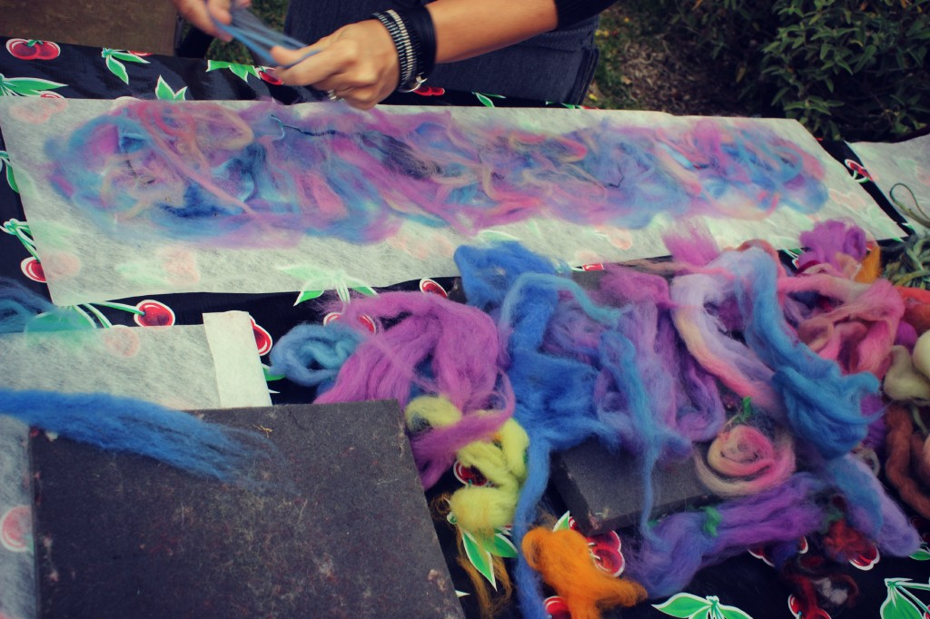 130123 Renuka laying down thin strips of colored roving on her Artfelt paper