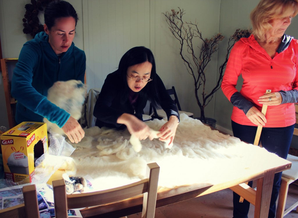 130130 Rebecca and Josephine applying white roving to pat pre-felted wool base for playscape.