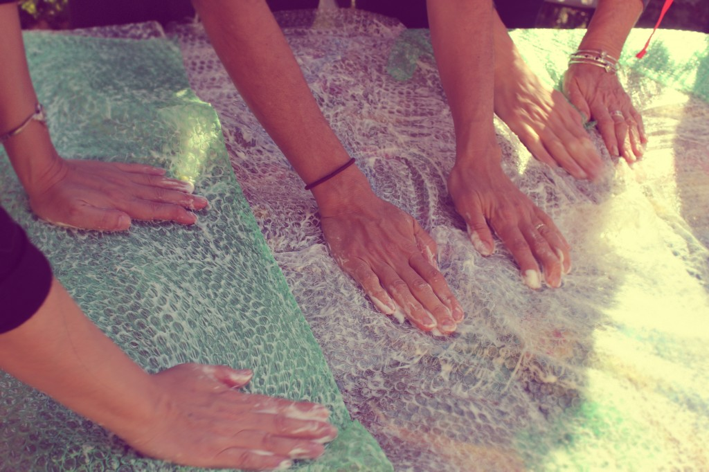 130130 many hands tapping on bubble-wrapped wet-felted blanket to felt the wool