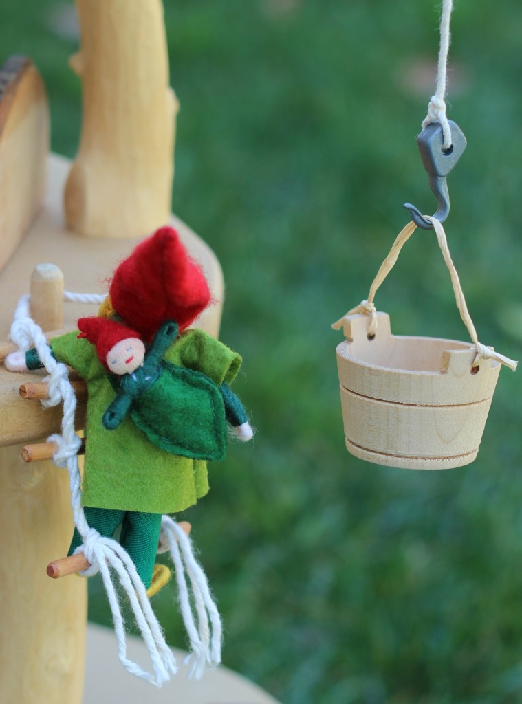 130226 Miniature gnome mommy with gnome baby on her back climbing a rope ladder up her magic fairy tree house