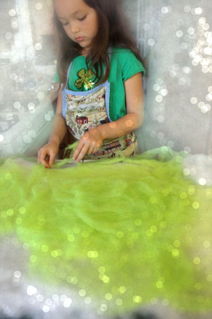 130405 Nunu adding thin, flat layers of chartreuse wool roving to wet-felted playscape project