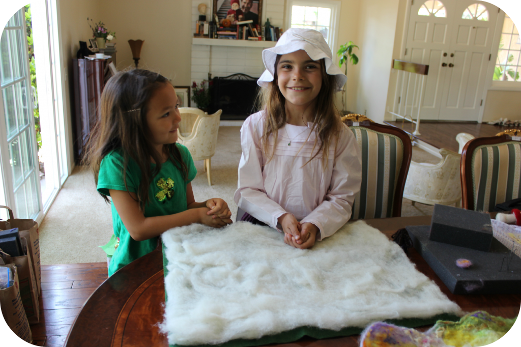 130404 Nunu and Anicka layering flat, thin layers of white batting to make wet-felted Waldorf playscape blanket mat