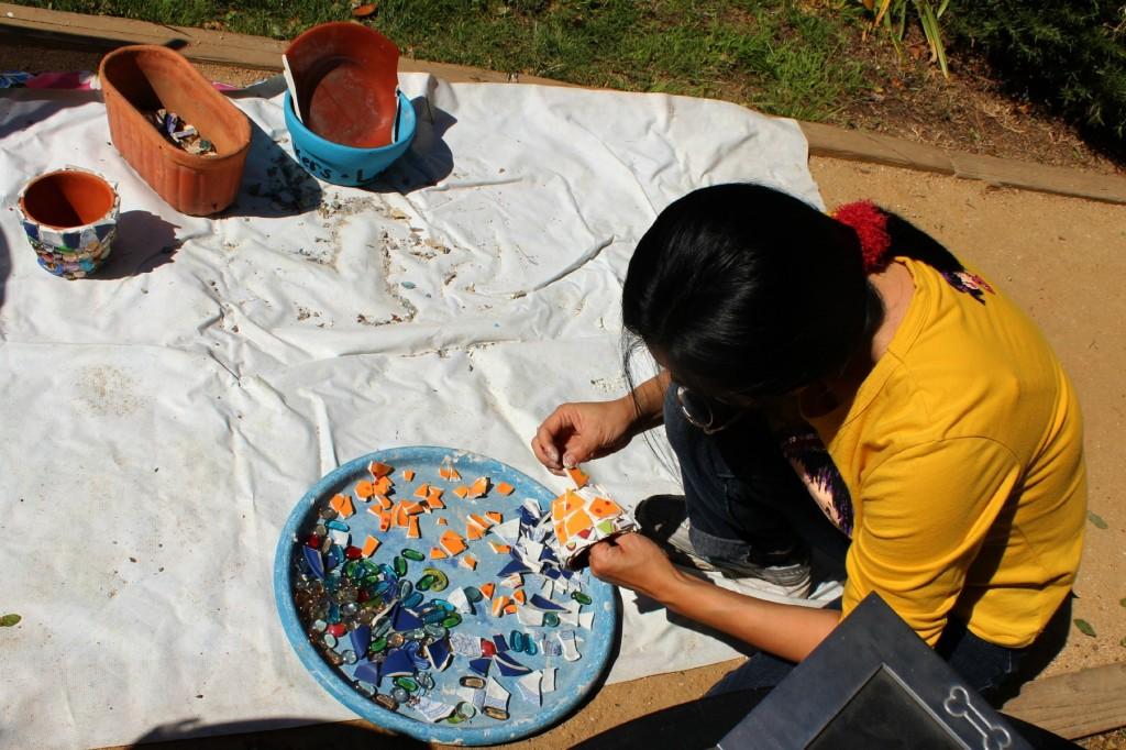 130410 Josephine carefully selecting broken tiles to arrange on her mosaic miniature flower pot