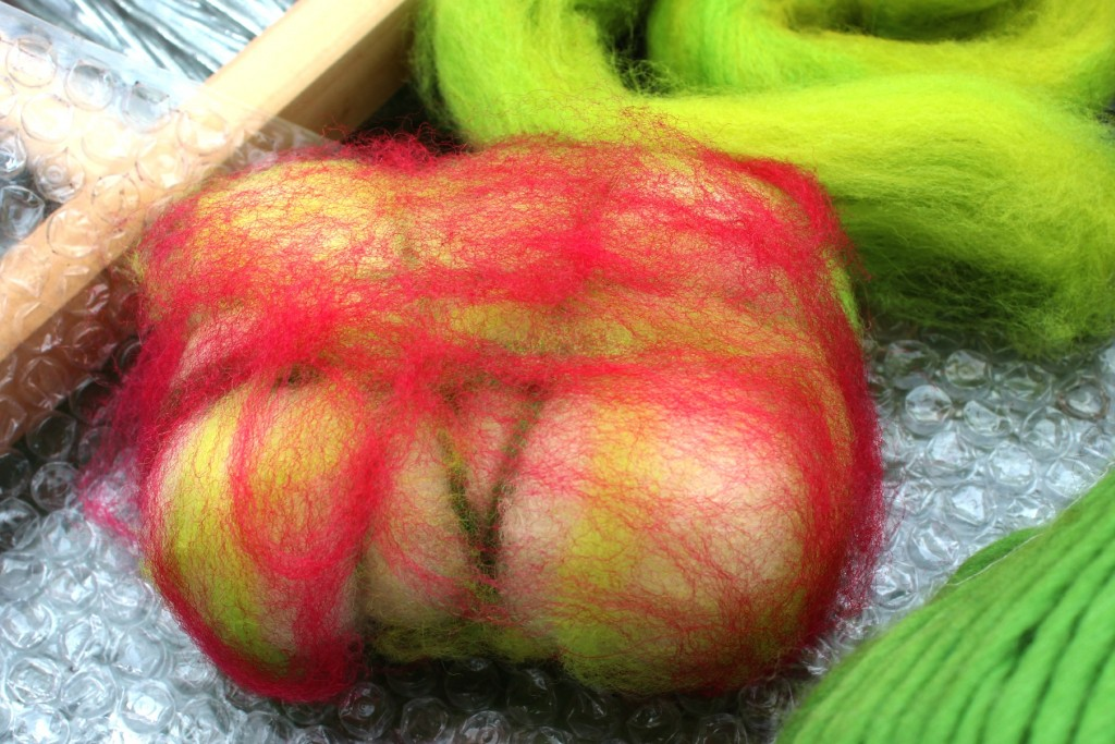 130501 soap wrapped in thin layers of chartreuse and rose red corriedale wool top roving and lime green pencil roving