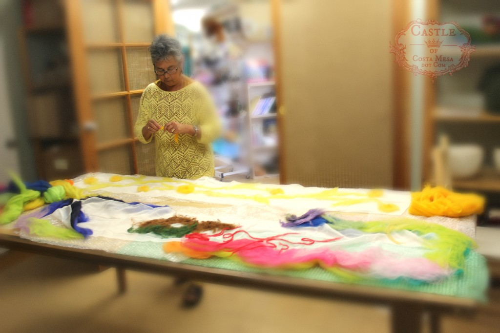 130522 Gaby arranging wool top fibers on her white silk chiffon nuno felting project on the long table