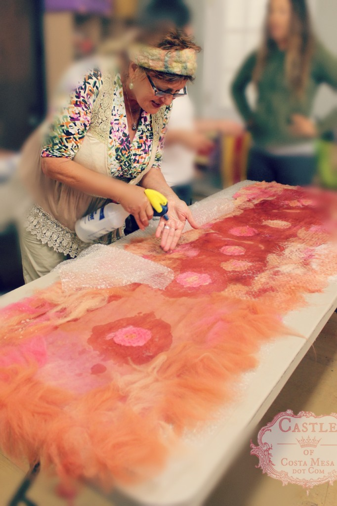 130522 Gisela carefully spraying hot soapy water onto her wool fiber designs on her silk chiffon scarf