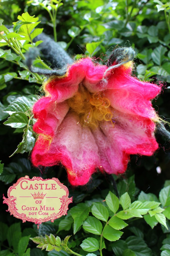 130605 Jzin's wet-felted trumpet shaped flower with long stem drying over honeysuckle hedge.