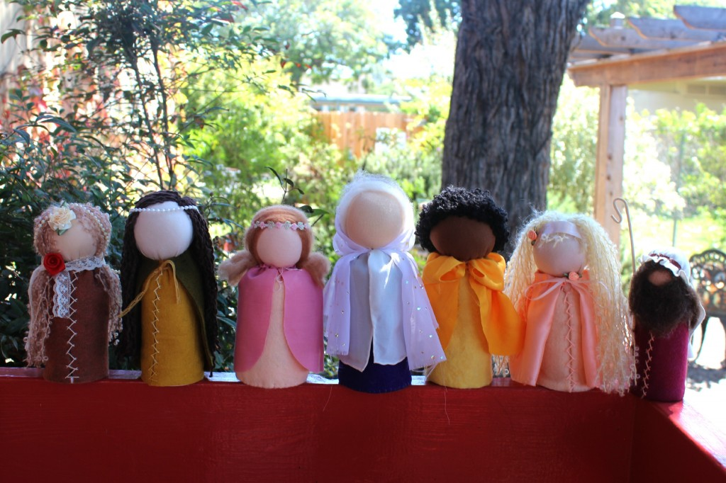 131001 7 table top puppets lined up on railing by Company of Angels store
