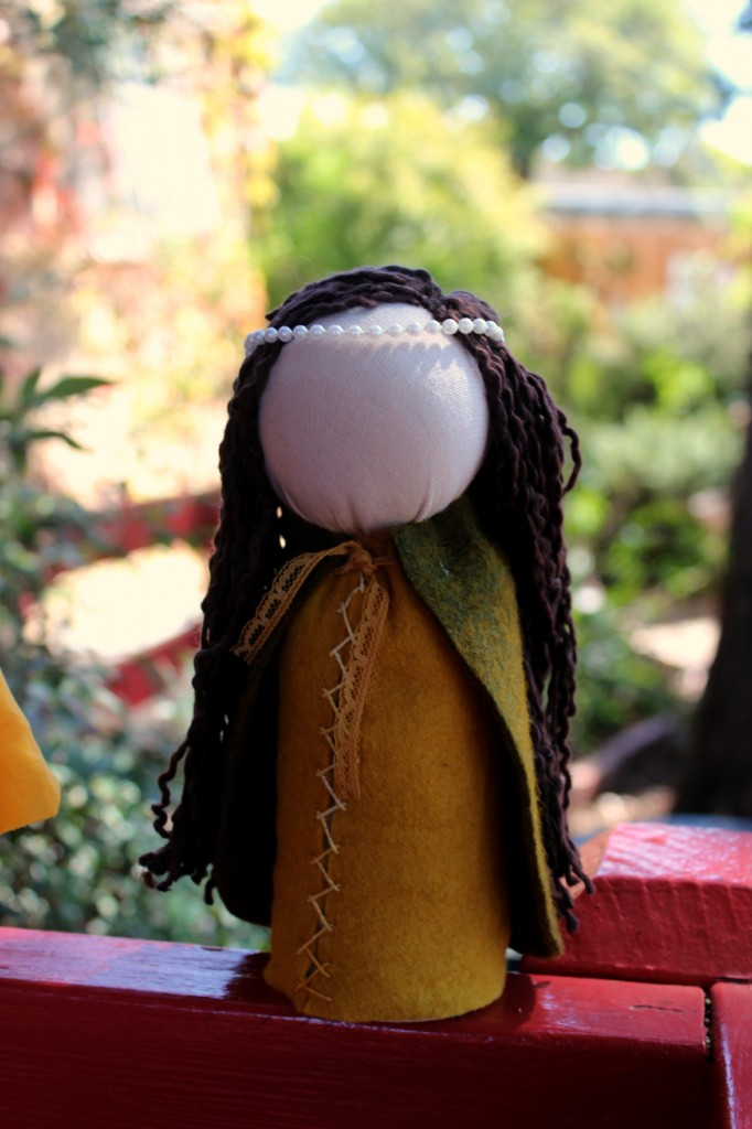131001 Yasmine's handmade renaissance princess table top puppet doll with long brown hair and pearl head dress on red railing