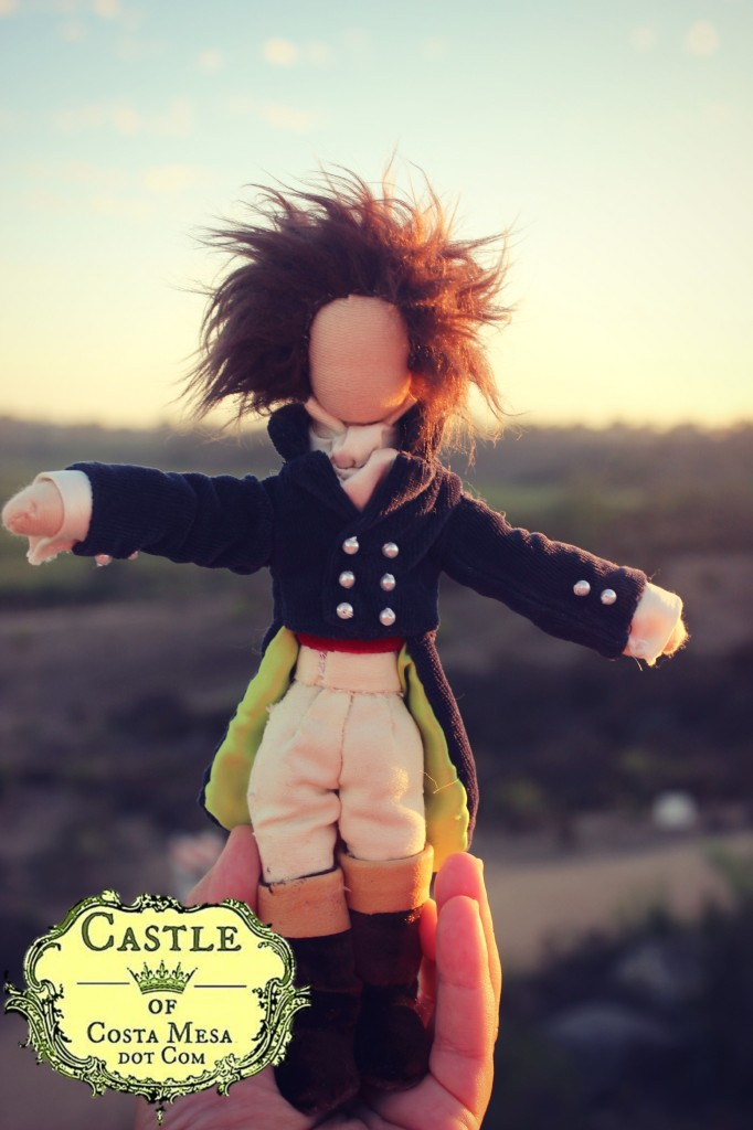 131002 Hans the Composer doll in sunset held by hand with logo