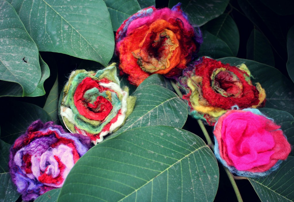 131007 5 wet-felted flowers embellished with mawata silk hankies made by craft group sitting in cherimoya tree