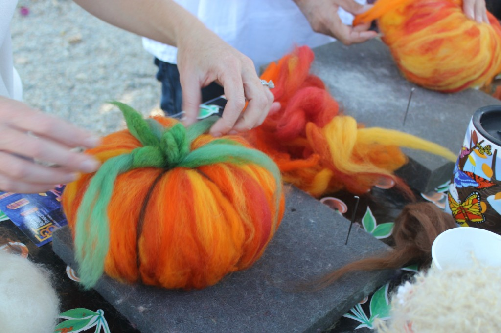 131015 Gina adding stems, leaves and tendrils to her felted pumpkin craft project.