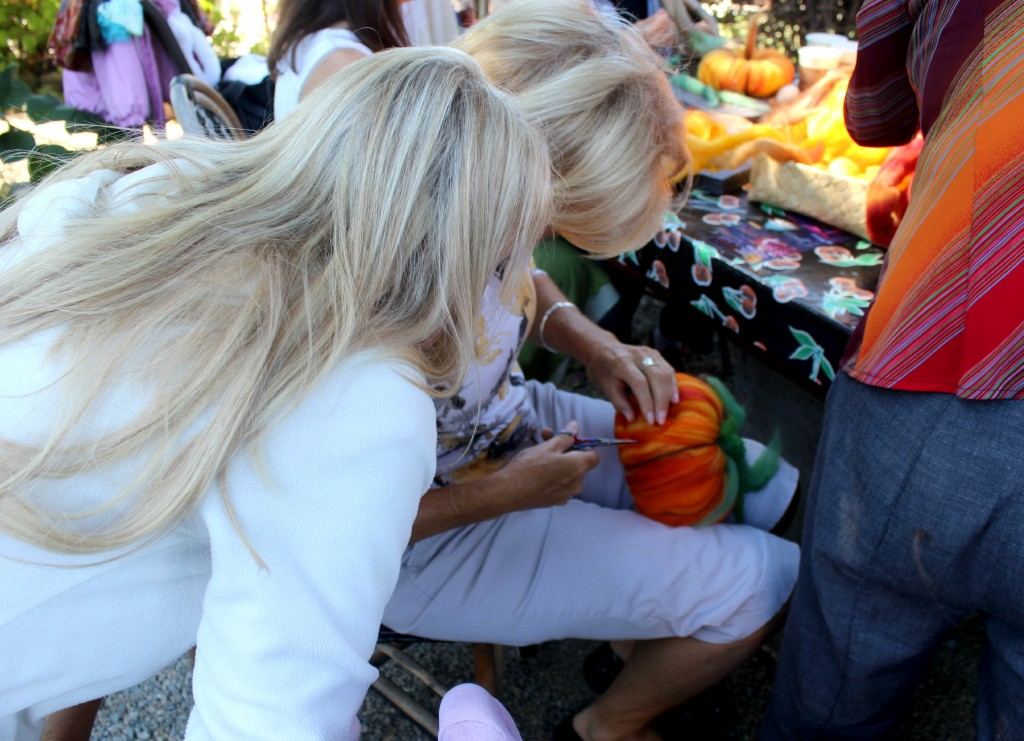 131015 Gina watching Christine cut a hole into her needle-felted pumpkin to make a door