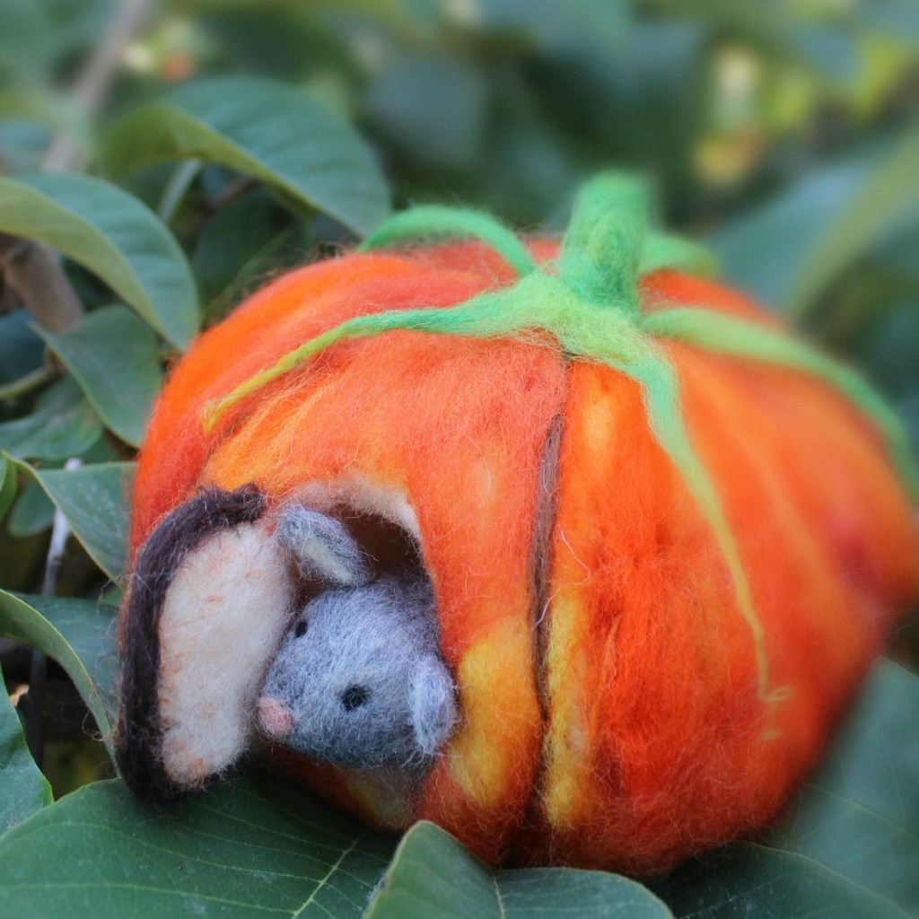 131015 square cropped. Josephine's needle-felted mouse peering out the door of his orange pumpkin house front door on foggy morning