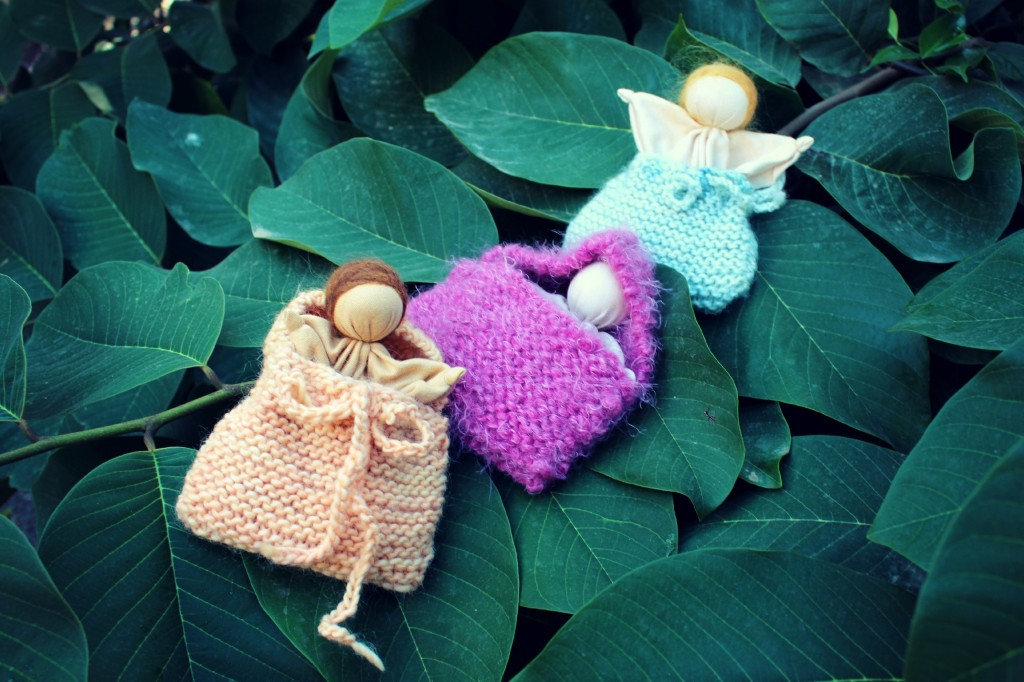 131029 3 Simple Waldorf Style Handmade hanky baby dolls in knitted blanket bags on cherimoya tree.