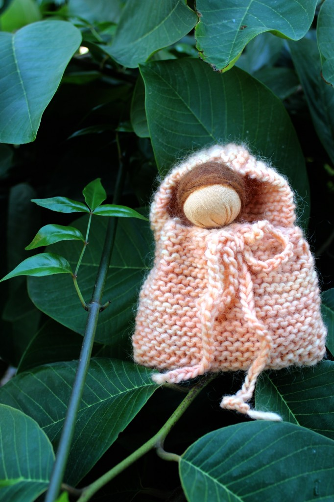 131029 Josephine's handmade simple Waldorf baby hanky doll in a knitted blanket bag on the cherimoya tree
