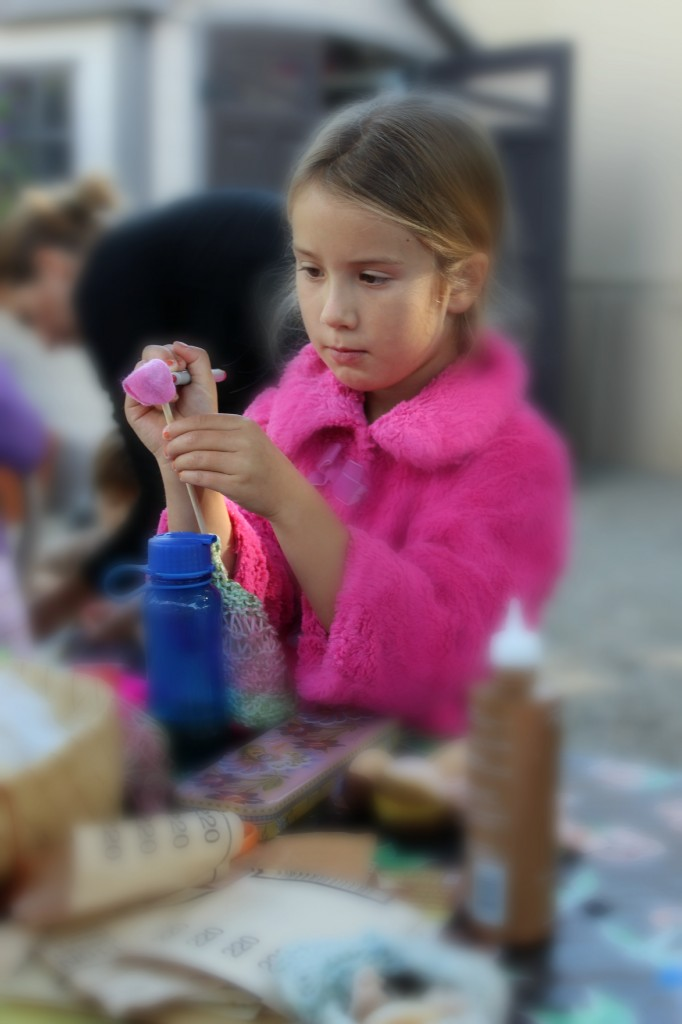 131029 Mia concentrating while drawing a face on her wooden handmade knitting needle doll