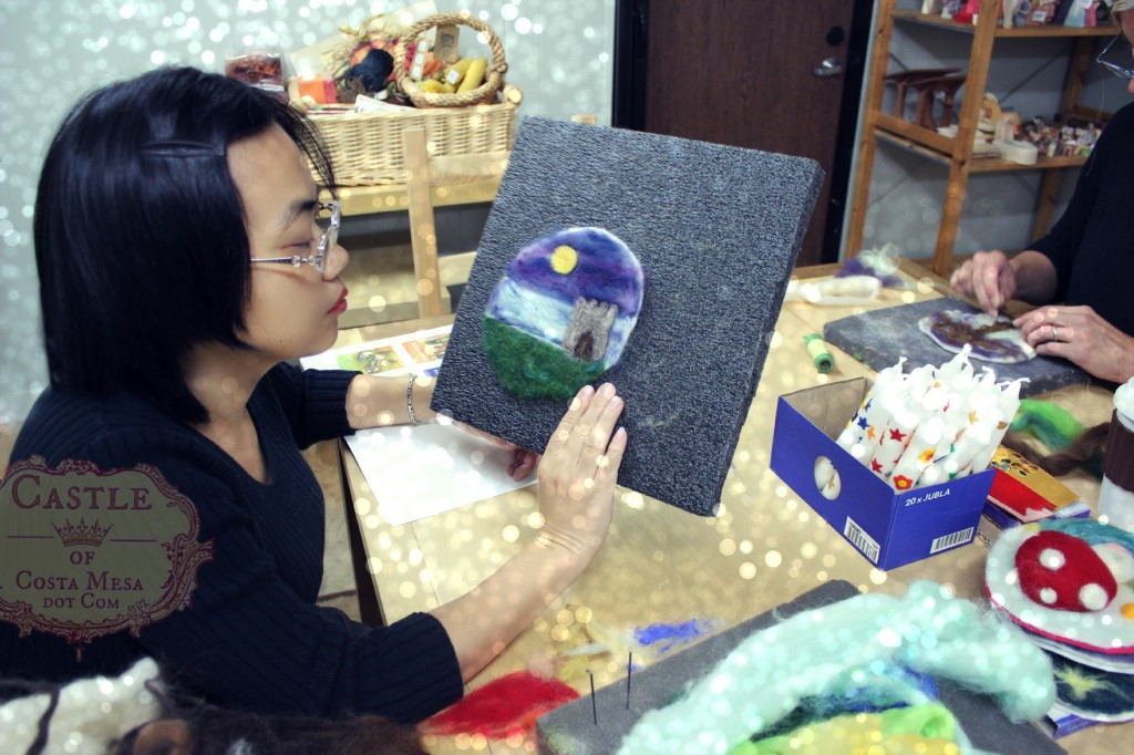 131203 Josephine composing her wool needle-felted picture of a castle in the moonlight on prefelt disc
