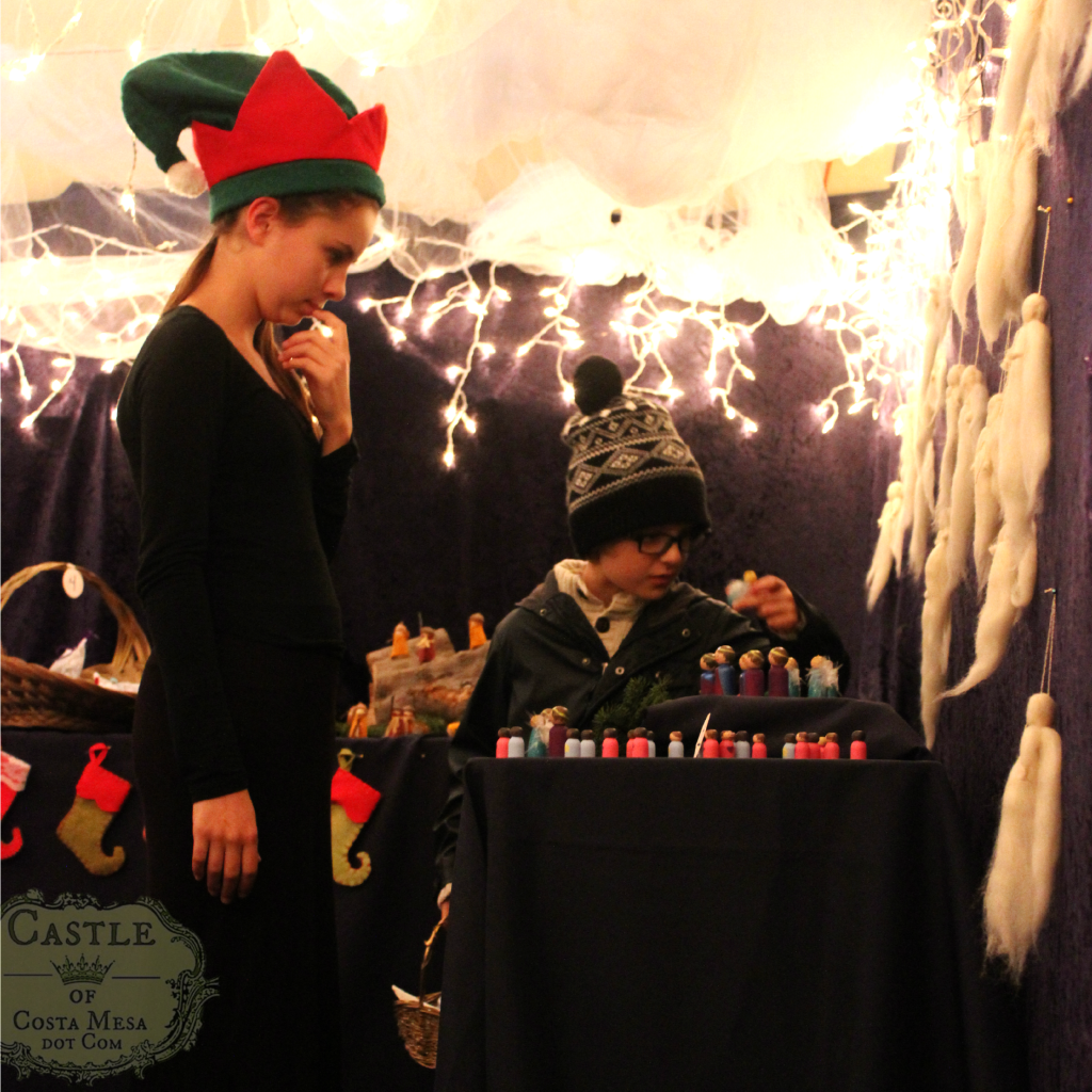 131209 Little boy examining painted wooden peg doll with elf looking on