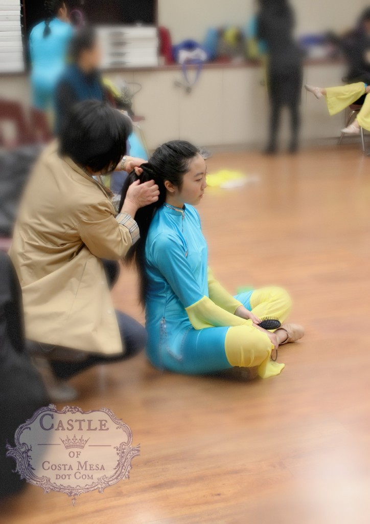 140202 Mother tying teenage daughter's hair for folk dancing