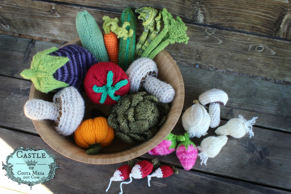 140310 Knitted and Crocheted Stone Soup vegetables and ingredients on bench under magnolia tree with logo
