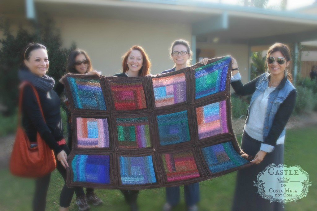 140305 5 women holding up Kim et all community knitted afghan blanket. With logo