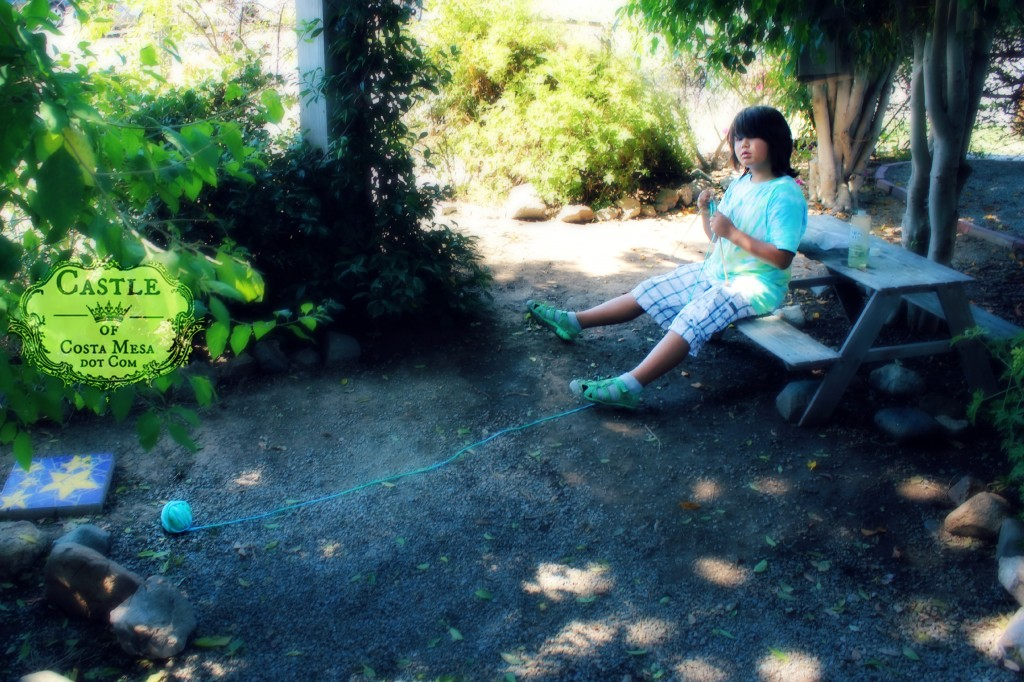 140916 Adrian knitting in the dappled woods with a runaway ball of yarn 2