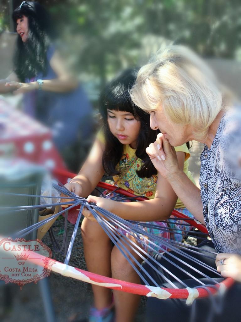 140922 Katya making bath rug loom with hula hoola hoop and strings with Christine Newell looking on 2