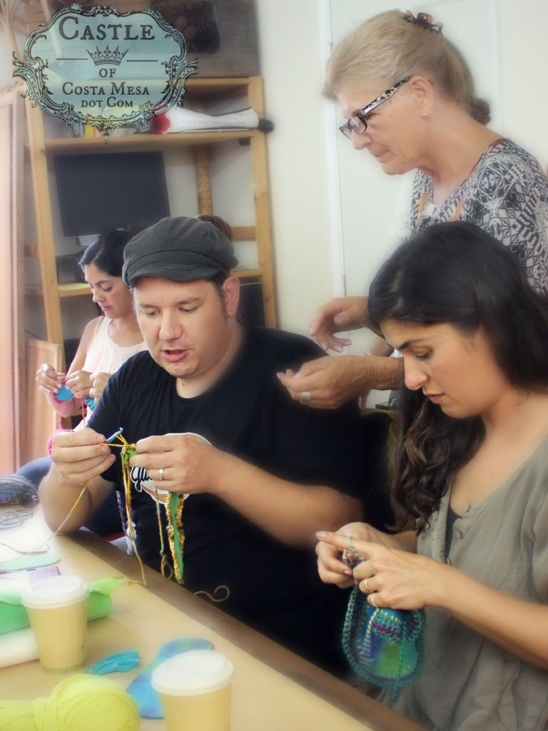2764 150915 Josh crocheting a pair of slippers for his wife flanked by Yvonne, Christine and Roxanna
