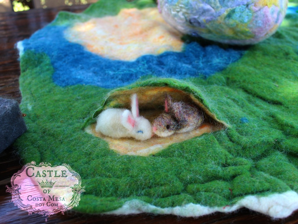 5350 160309 Needle-felted white and Heather colored bunnies with pink noses in a burrow